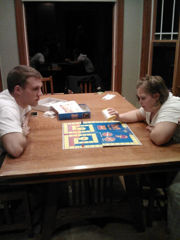 Amy likes to play board games. Daniel is home for a few weeks and is showing Amy how to play.